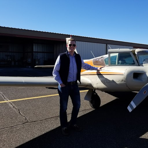Man in a black vest smiling next to a plane.