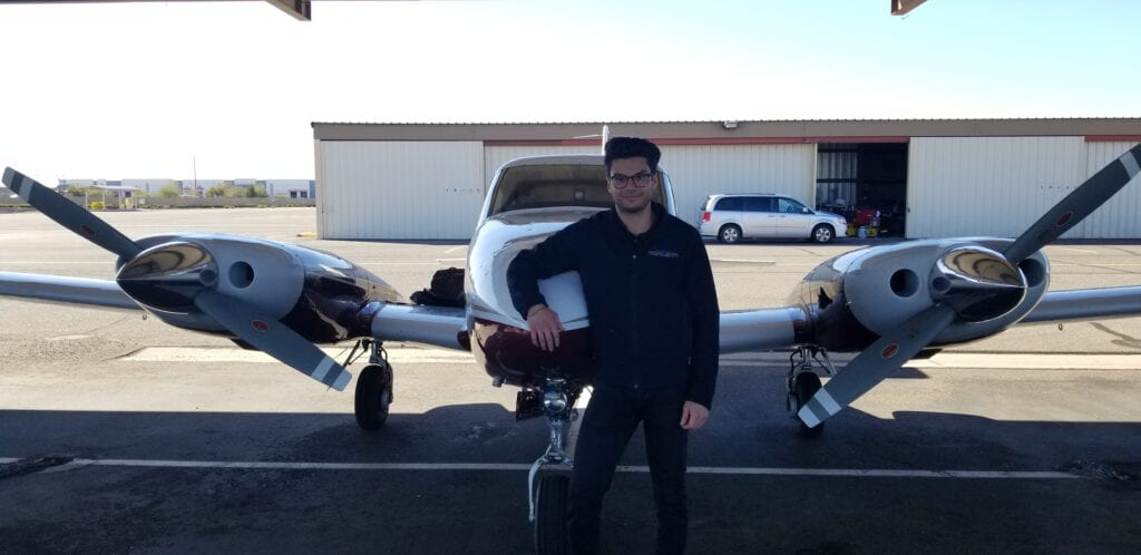 Man with eye glasses in front of an aircraft.
