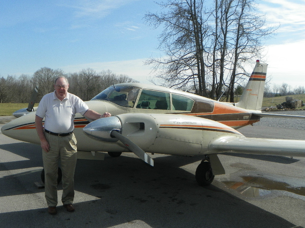 An old man posing in front of a plane.