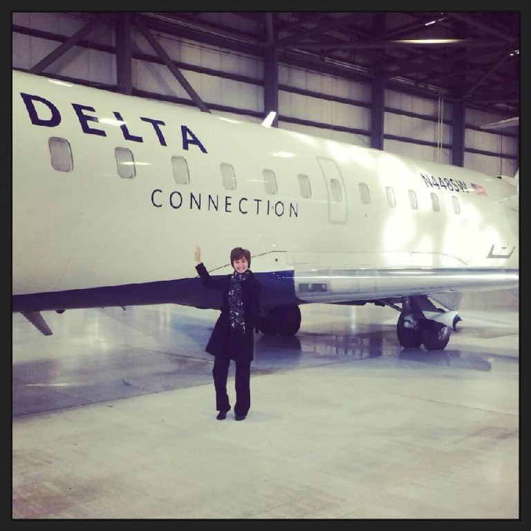 A woman taking a photo with a Delta airplane.