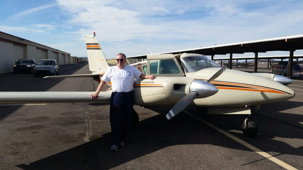 Old man in a white shirt smiling next to an aircraft.