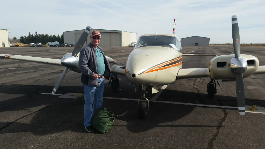 Old man in a gray jacket in front of an airplane.