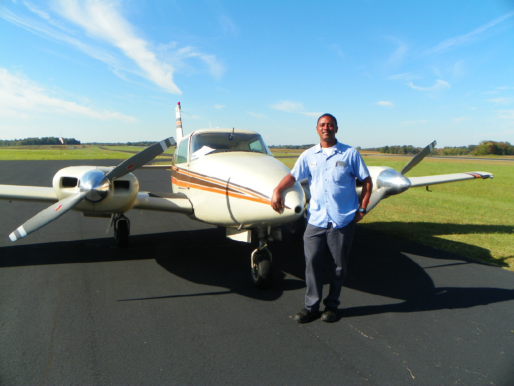An African-American man posing in front of an aircraft.