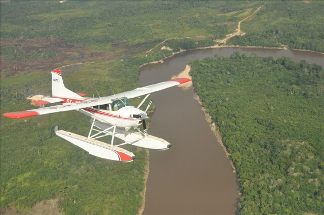 A small aircraft flying over the river.