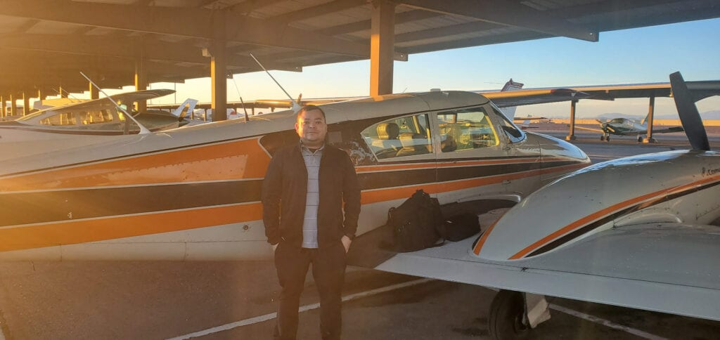 Man in a black jacket and black pants in front of a plane.