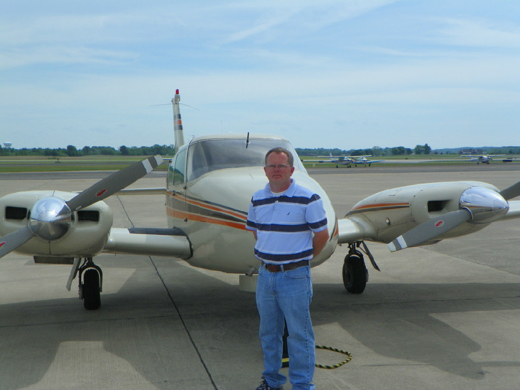 A Caucasian guy in a striped shirt standing in front of an airplane.