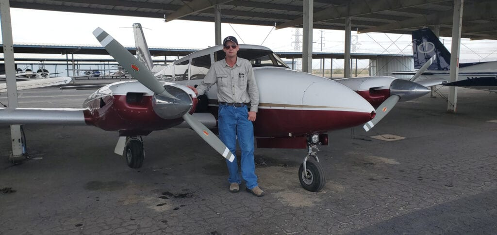 Man in a long-sleeved shirt posing next to a plane.