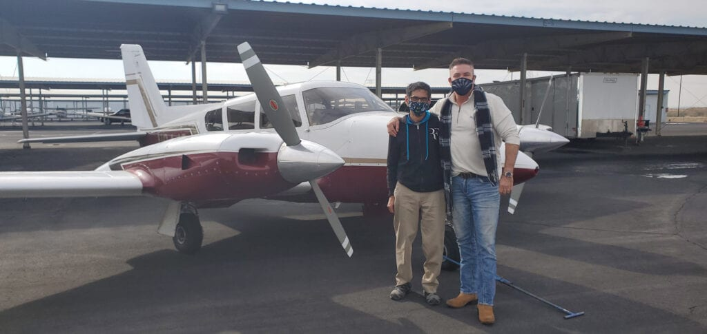 Two men in face masks in front of a plane.