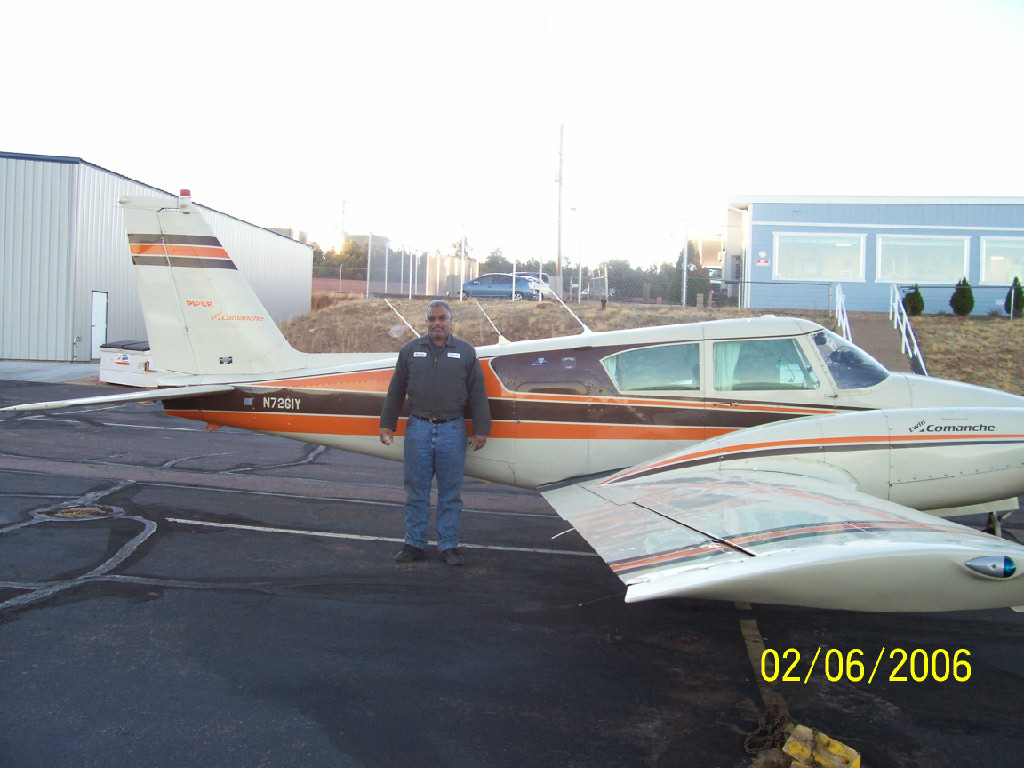 An old African-American man beside an airplane.