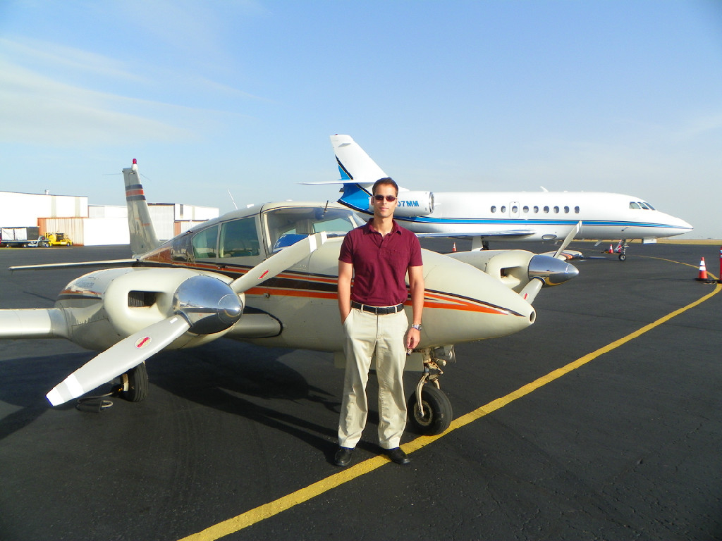 A tall guy wearing a maroon shirt standing in front of a plane.