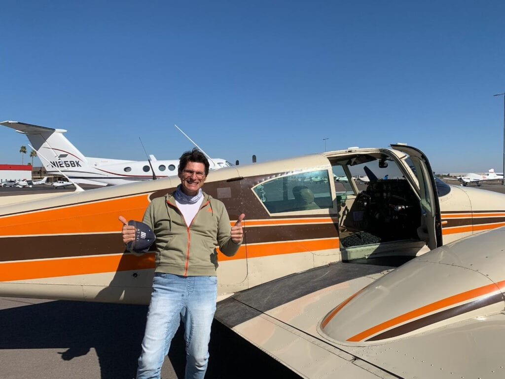 Man in a brown jacket next to an aircraft.