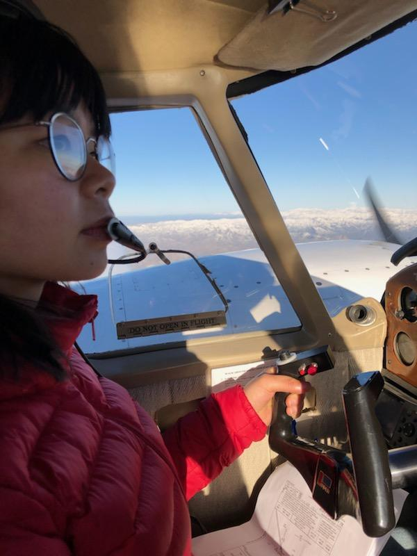 Asian woman flying an airplane.