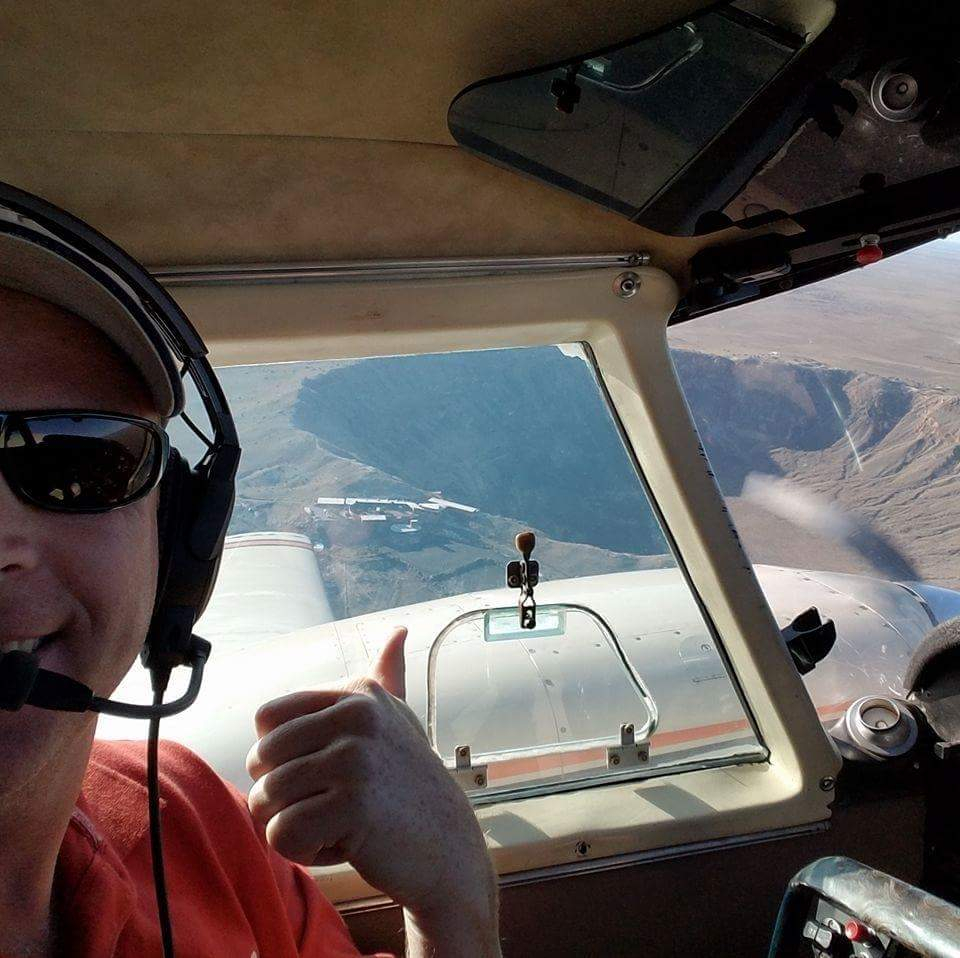 Man in a red shirt flying a plane.