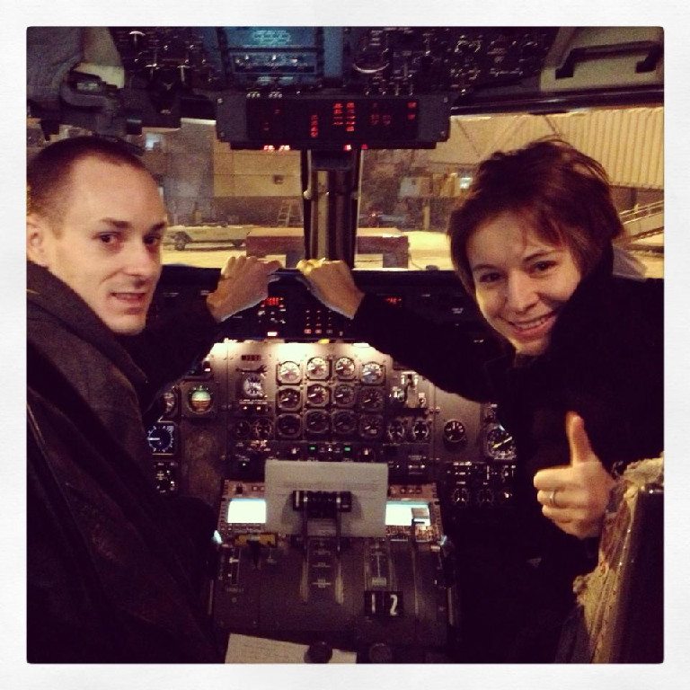 A male and female pilot inside the cockpit.