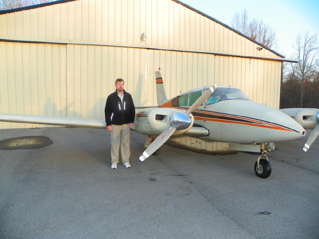An adult standing beside an airplane.