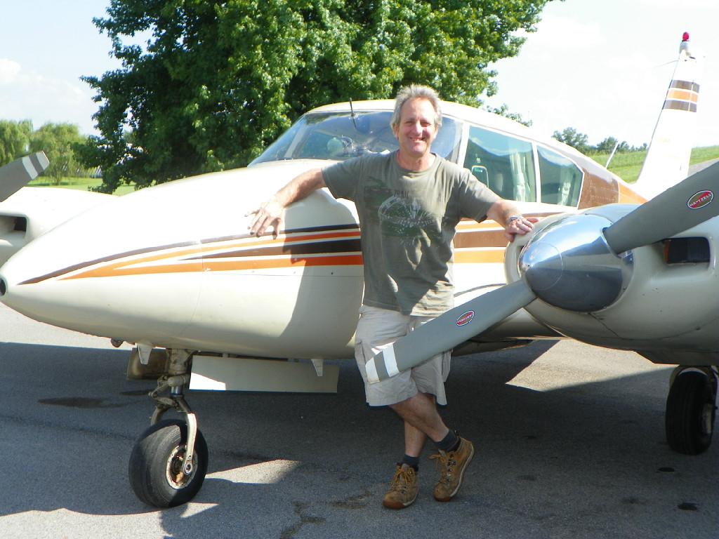 A Caucasian man in a gray shirt standing beside an airplane.