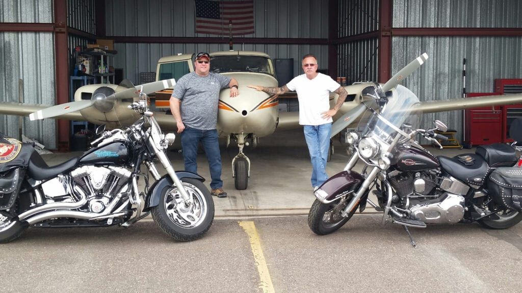 Two men posing with an airplane and motorcycles.