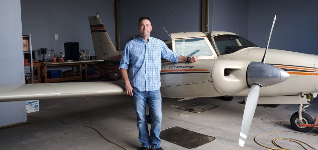 Man in a blue long-sleeved shirt next to a plane.