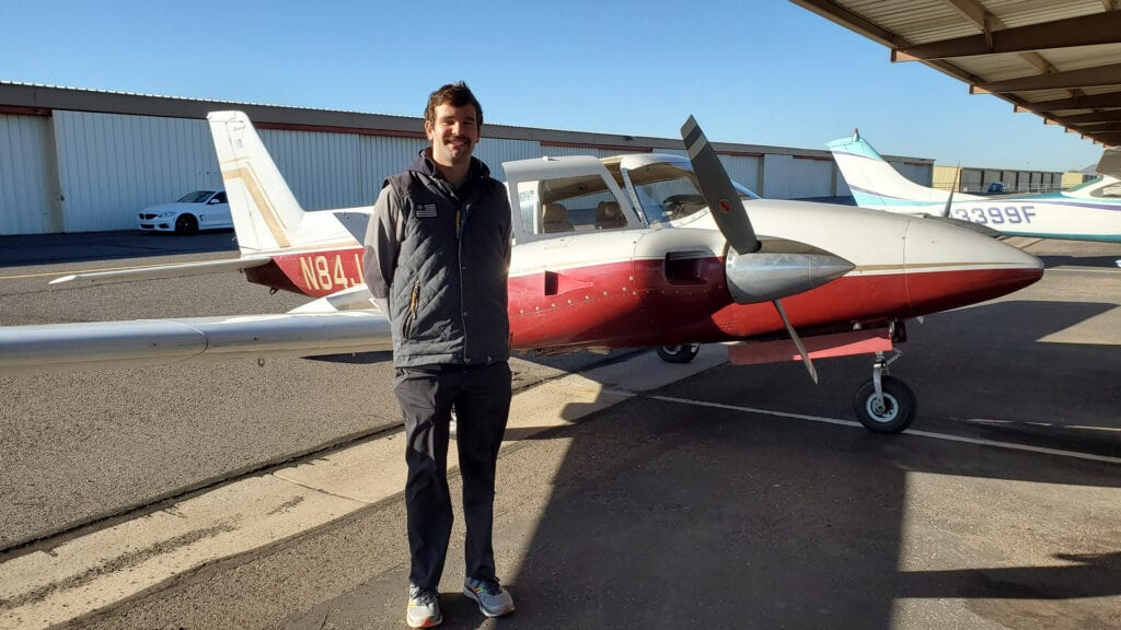 Person standing in front of a Piper Twin Comanche.