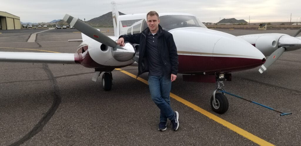 Man in a black jacket smiling and leaning against an aircraft.