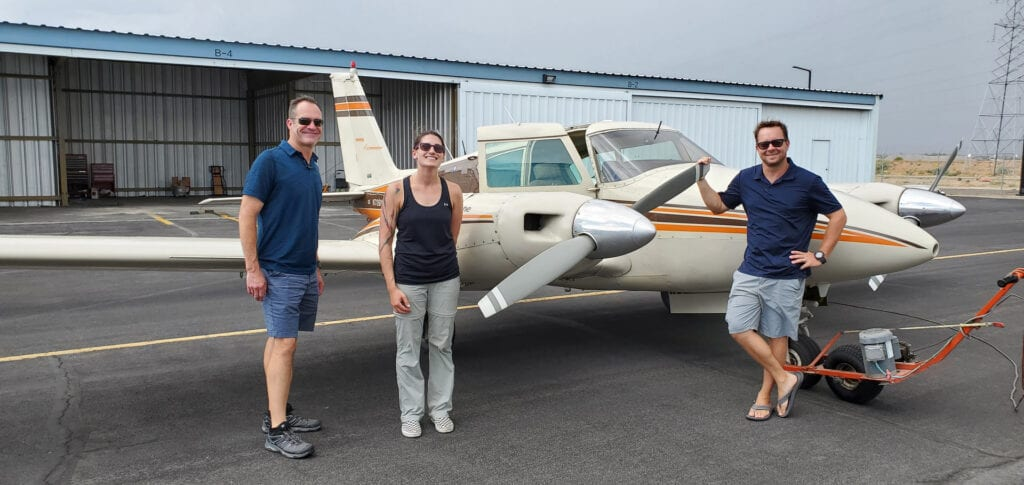 Two men and one woman smiling next to a plane.