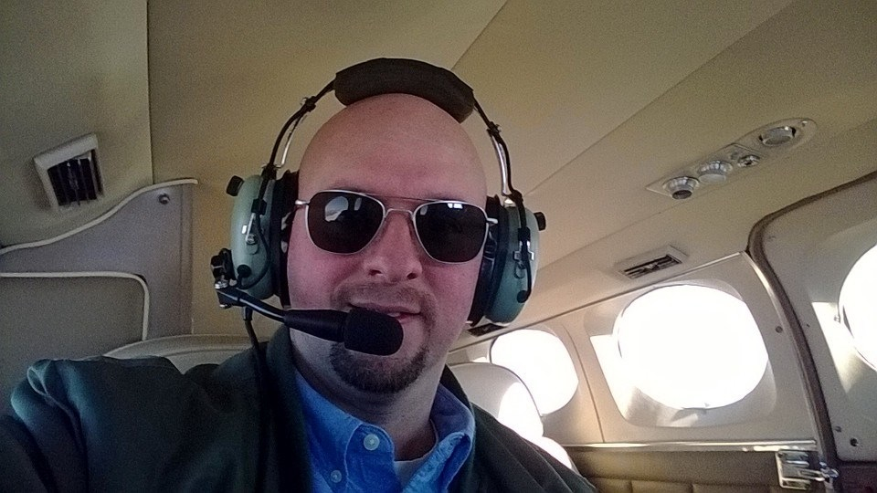 A bald man taking a selfie inside the plane.