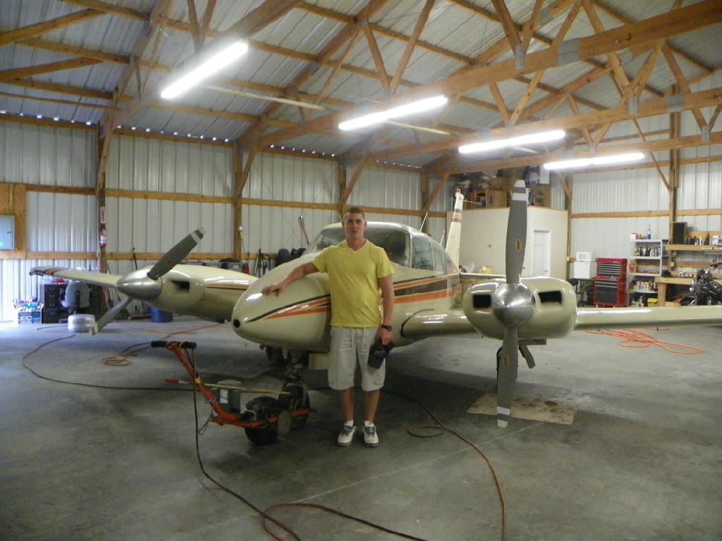 A man wearing a yellow shirt posing with a plane inside the hangar.
