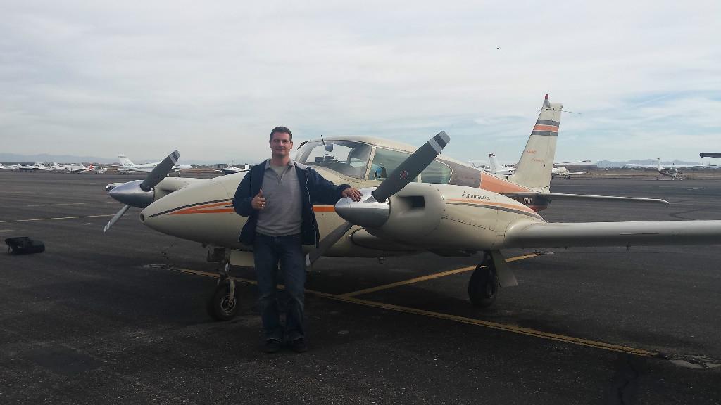 A Caucasian guy posing next to a Piper Twin Comanche.