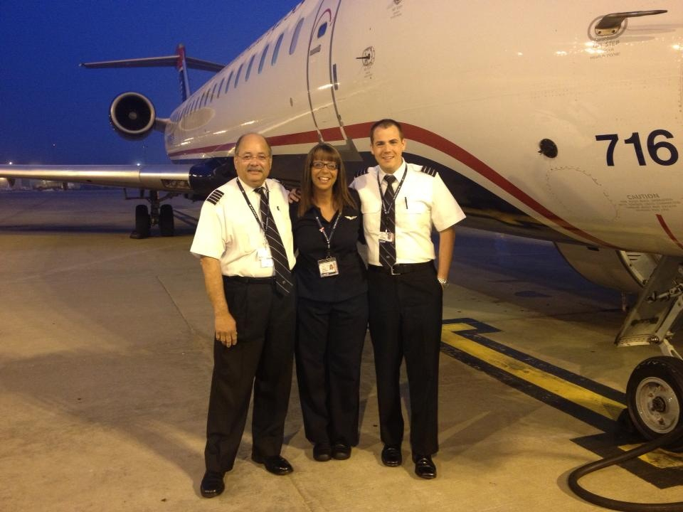 Three pilots posing in front of an airplane.