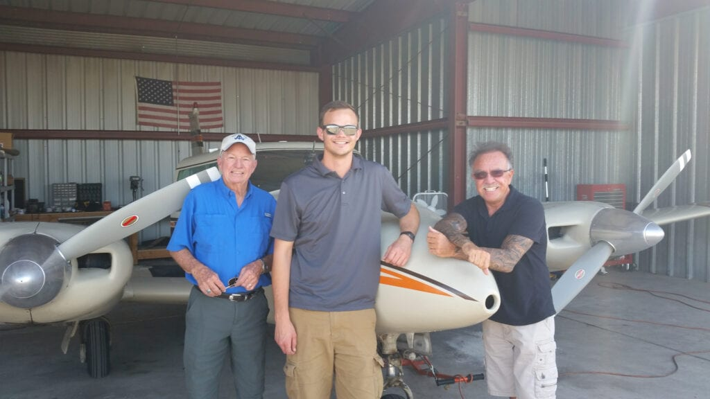 Three people posing next to a small aircraft.