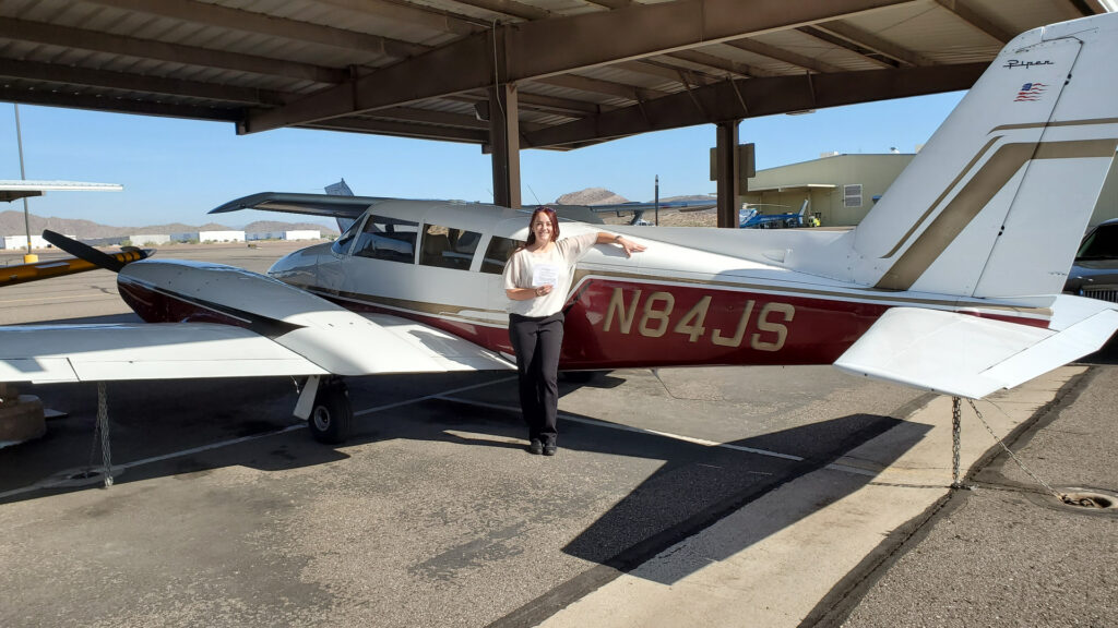 Woman in a white shirt standing next to a plane.