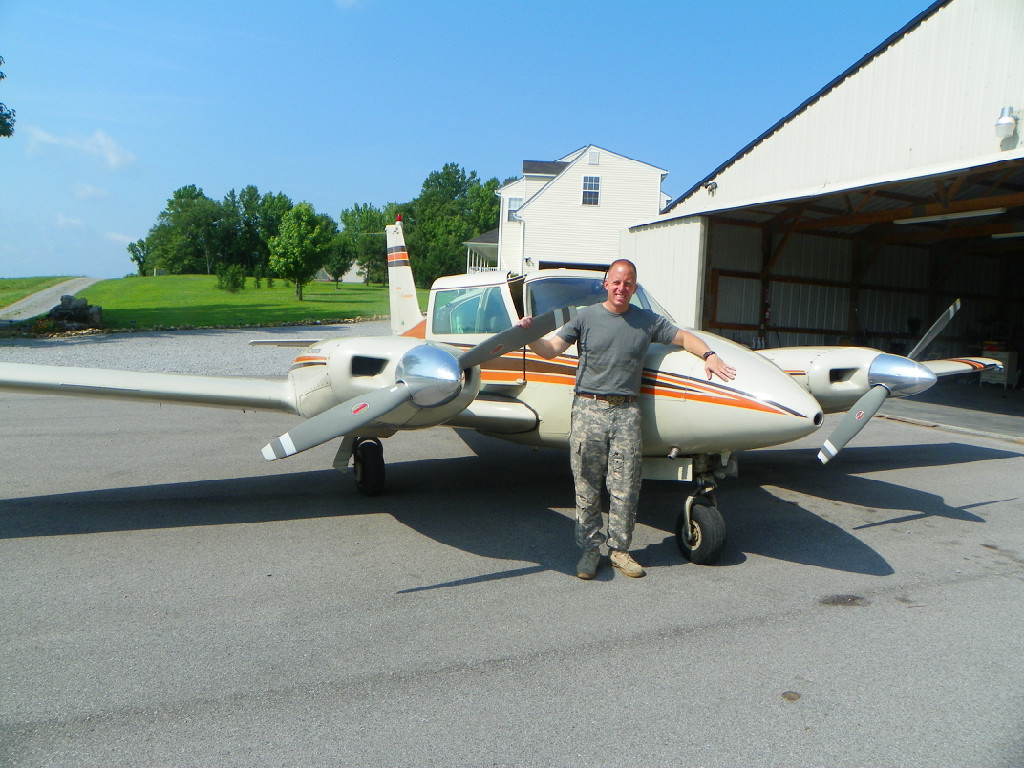 A man wearing camouflage pants standing in front of an airplane.