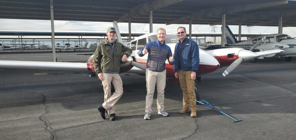 Three men posing in front of an airplane.