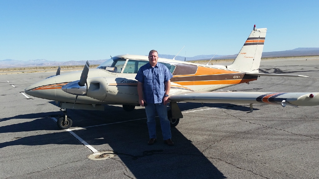 A Caucasian guy wearing a checkered shirt standing next to a plane.