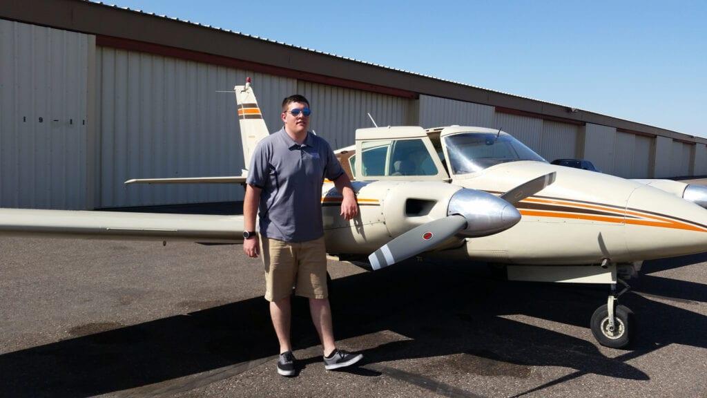 Person wearing a dark blue shirt next to an airplane.