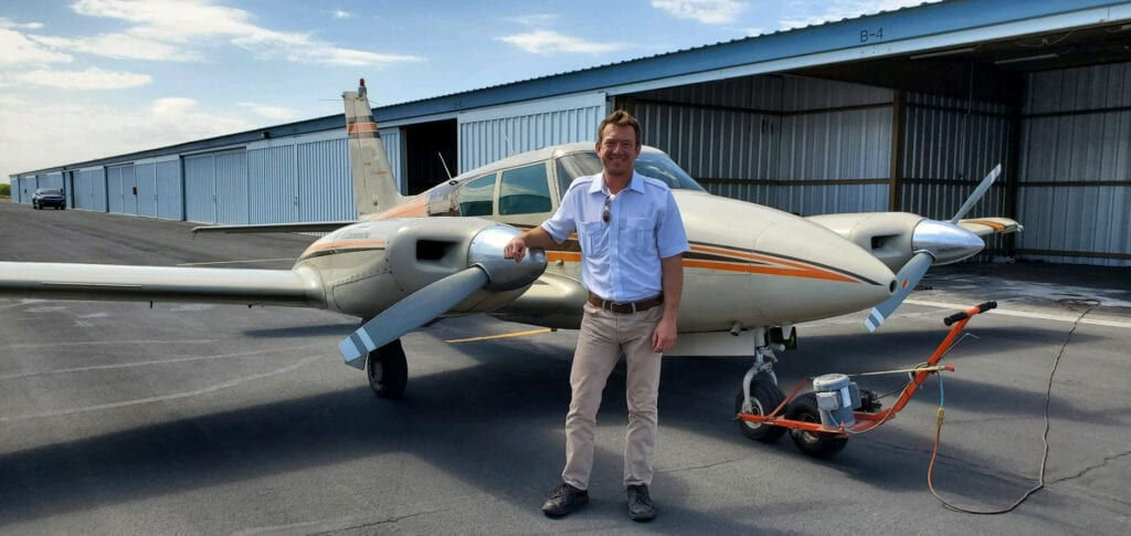 Man in a light blue shirt in front of an aircraft