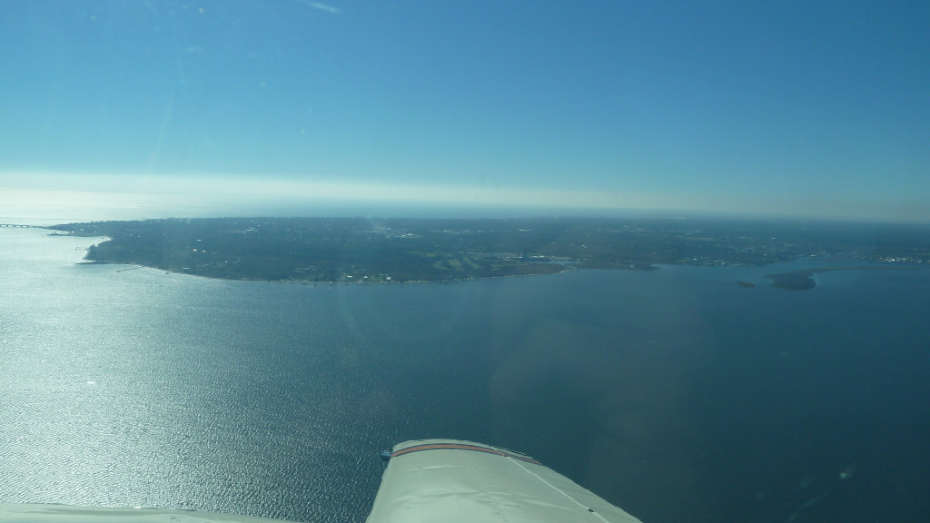 A plane flying over a large body of water.