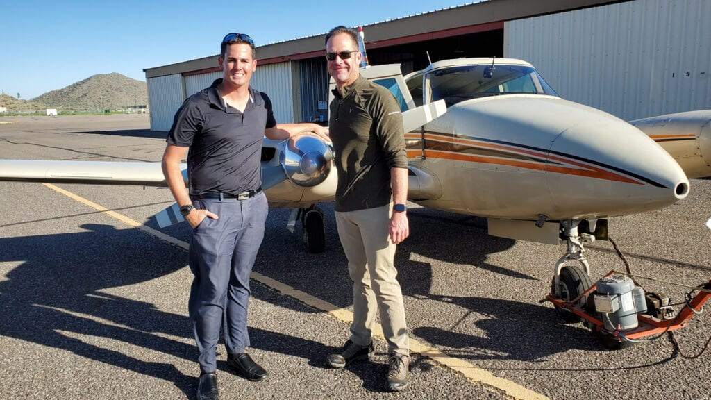 Two men posing in front of a Piper Twin Comanche.
