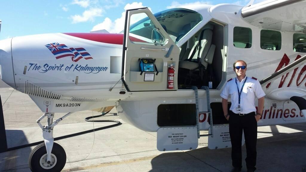 A pilot smiling beside an aircraft.