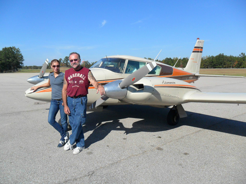 A man and a woman in front of a Piper Twin Comanche.