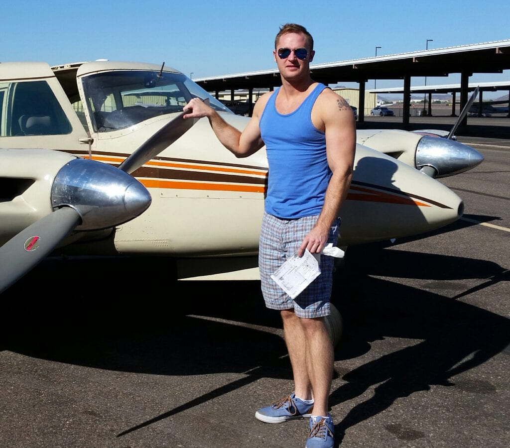 Man in a blue muscle tee posing next to a plane.