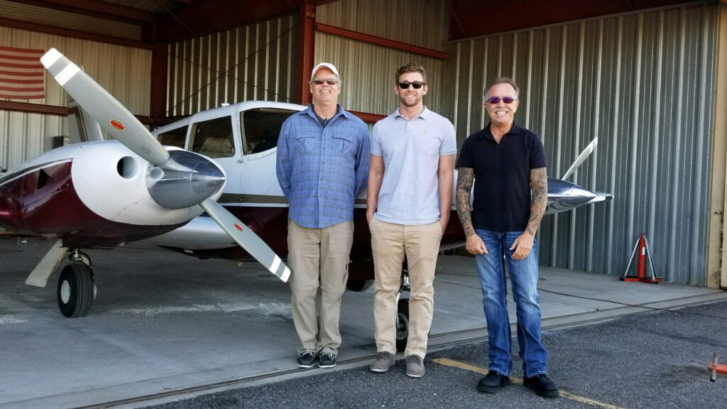 Three men standing in front of a small plane.