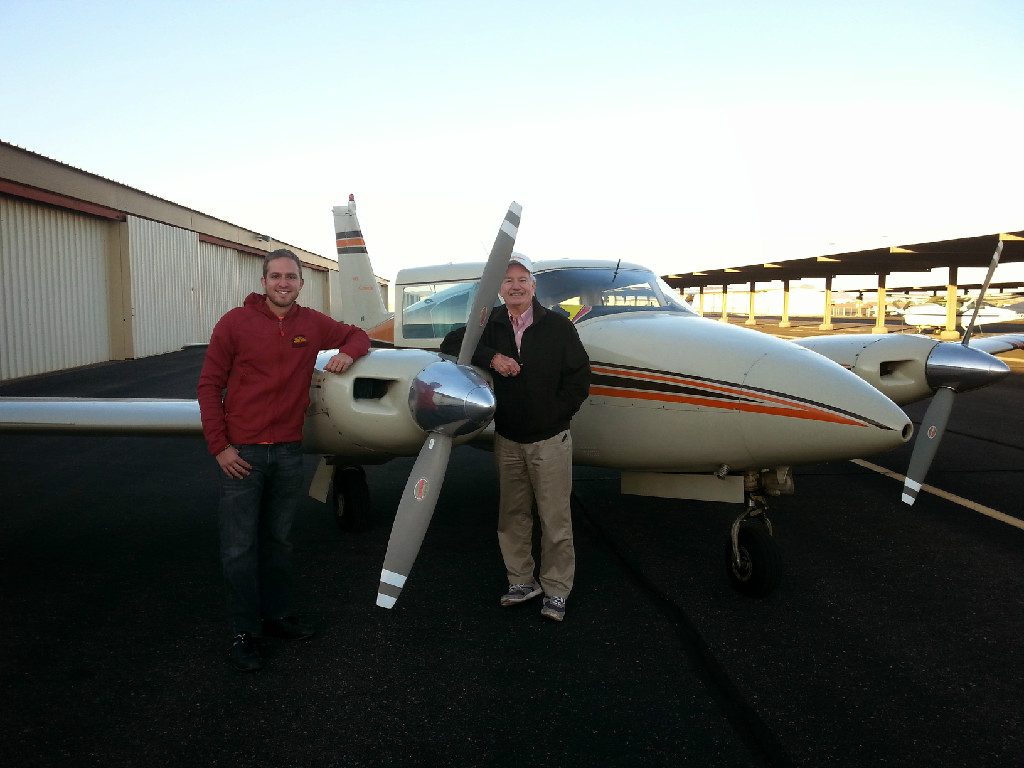 Two guys posing next to a propeller.