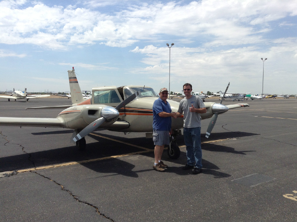 Two guys shaking hands in front of an aircraft.
