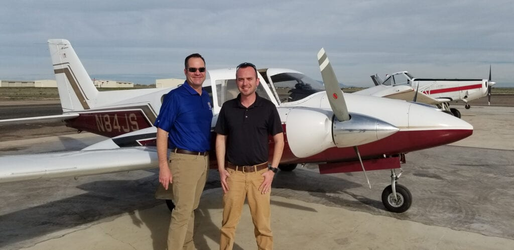 Two Caucasian men posing in front of a small airplane.