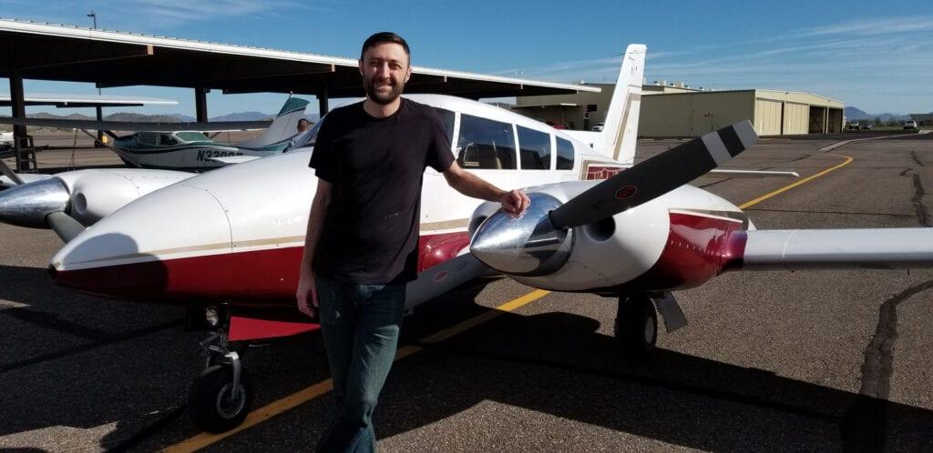 A person posing next to a small plane.