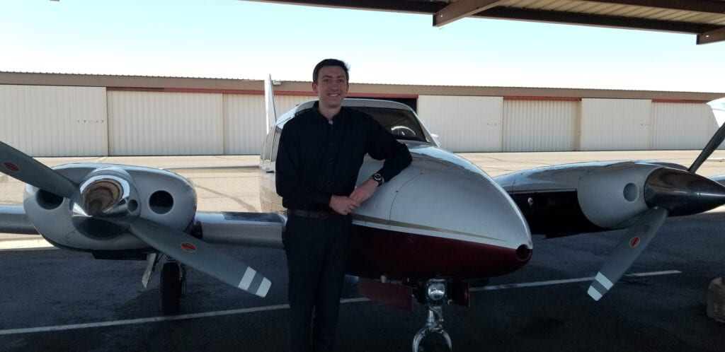 Man in a black long sleeved shirt next to a plane.
