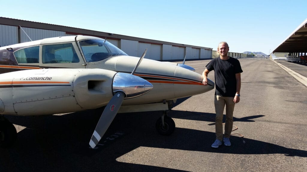 Person in a black shirt and khaki pants smiling next to a plane.