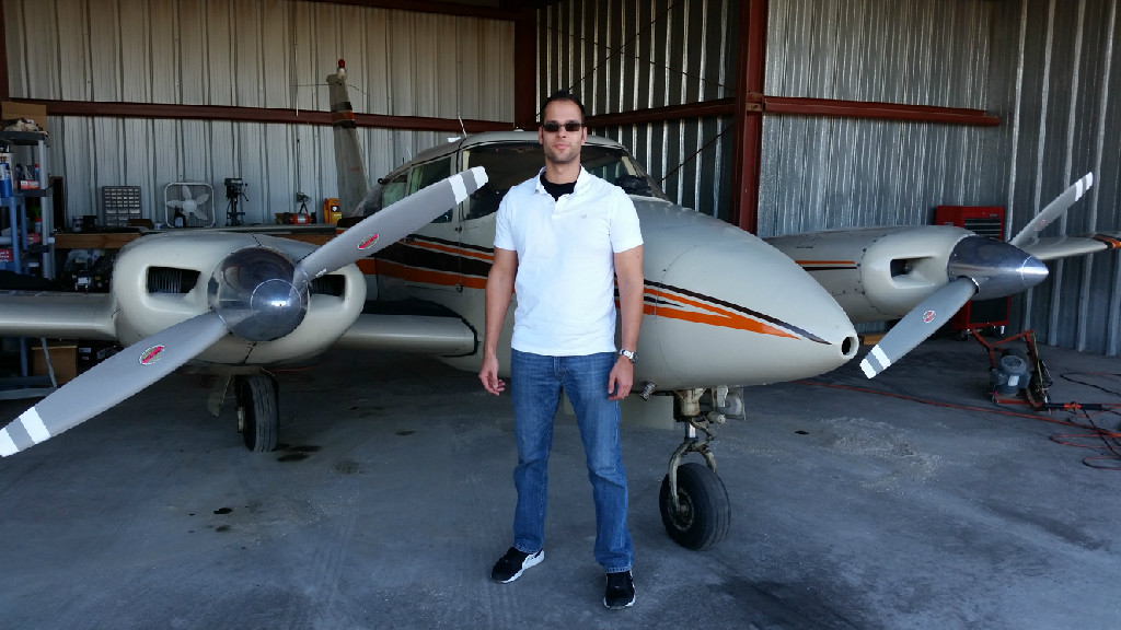 A guy wearing a white shirt and denim pants standing next to a plane.
