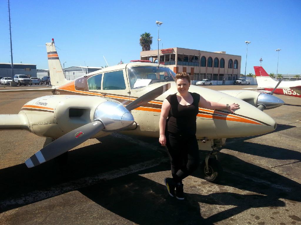 A woman posing next to a small plane.